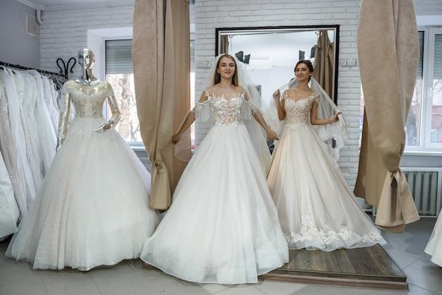 Gelukkige bruiden in trouwjurken poseren in salon