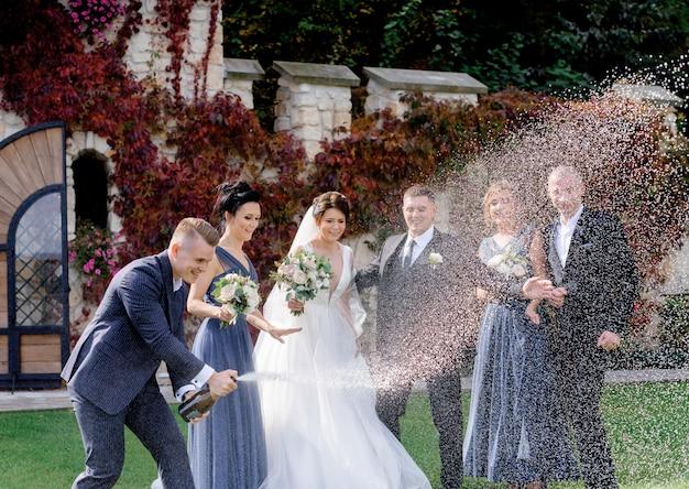 Gelukkige bruidsmeisjes, getuige mannen en bruidspaar viert trouwdag buitenshuis met het uitgieten van champagne