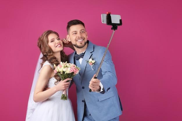 Gelukkige bruidspaar selfie maken op kleur achtergrond