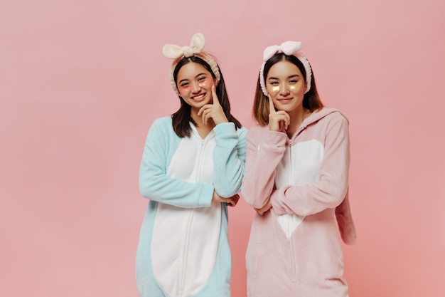 Gelukkige brunette aziatische meisjes in kigurumi's glimlachen oprecht op geïsoleerde