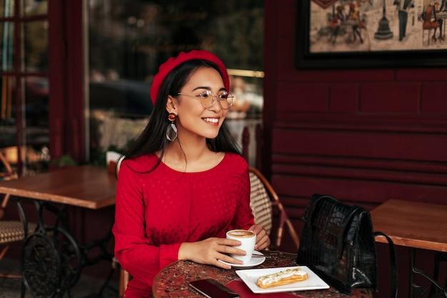 Gelukkige brunette dame in rode jurk en baret glimlacht oprecht