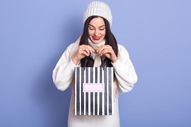 Gelukkige brunette die witte hoed, sweater en sjaal draagt, neer kijkend, houdend heden