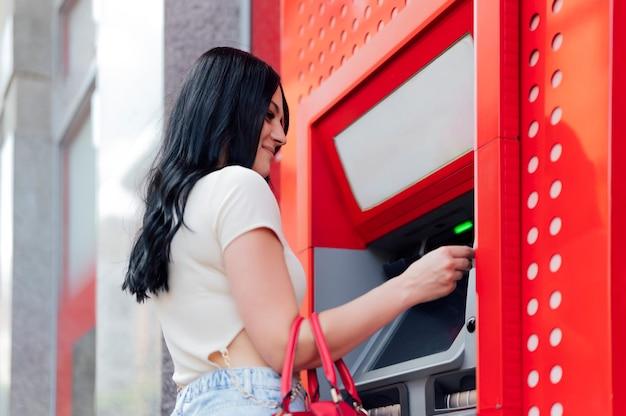 Gelukkige brunette vrouw die geld opneemt van creditcard bij atm