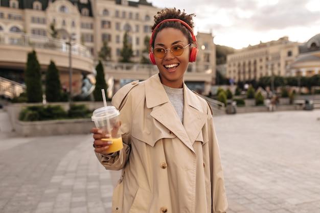 Gelukkige brunette vrouw in oversized beige trenchcoat luistert naar muziek in rode koptelefoon, glimlacht, houdt sinaasappelsap glas buiten