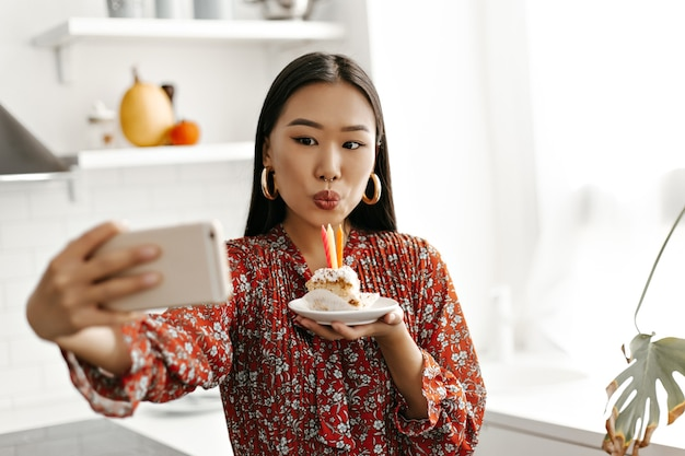 Gelukkige brunette vrouw in rode bloemenjurk neemt selfie en blaast kaarsjes uit op een smakelijke zoete verjaardagstaart