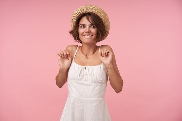 Gelukkige brunette vrouw met kort kapsel positief opzij kijken en haar onderlip bijten, witte jurk en strooien hoed dragen terwijl poseren met opgeheven handen
