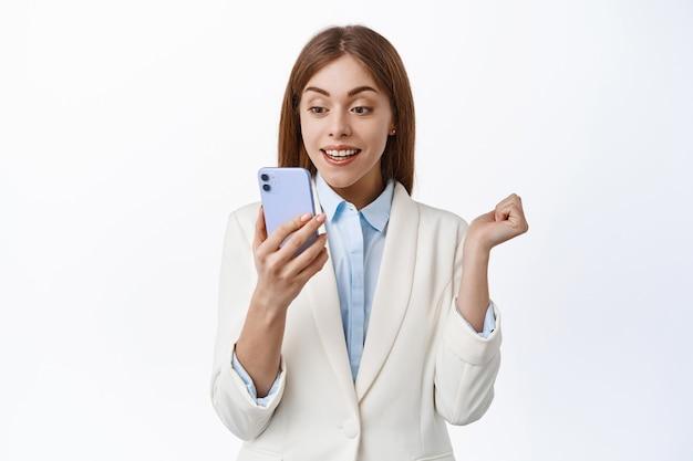 Gelukkige ceo-kantoorvrouw kijkt naar mobiele telefoon met opgewonden gezicht, leest smartphonescherm, wint online, ontvangt bericht met goed nieuws, witte muur