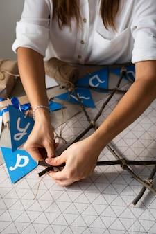Gelukkige chanoeka-vakantievrouw die een slinger maakt