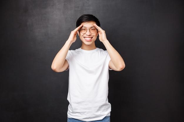 Gelukkige charismatische jongeman voelt zich goed, werd beter nadat hij medicijnen had voorgeschreven, glimlachte en hield zijn handen bij het voorhoofd alsof hij iets op afstand zag, vond een perfecte plek