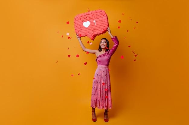 Gelukkige, charmante vrouw van 23 jaar houdt een bord in de vorm van een like van instagram vast en poseert in volle groei op een oranje muur met confetti