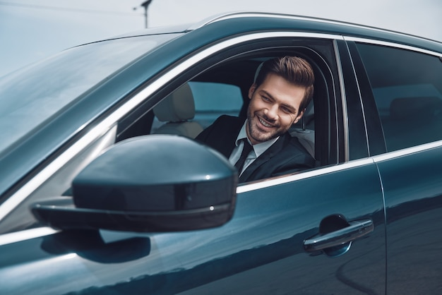 Gelukkige chauffeur. knappe jonge man in volledig pak die er recht uitziet tijdens het autorijden