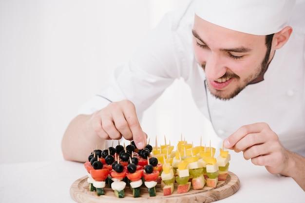 Gelukkige chef-kok die snacks op houten raad schikt