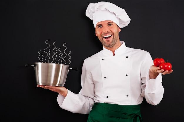 Gelukkige chef-kok die tomatensoep aanbeveelt