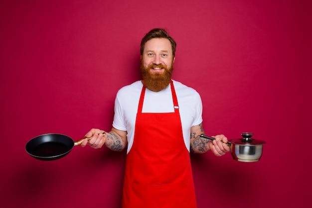 Gelukkige chef-kok met baard en rode schort kookt met pan en pot