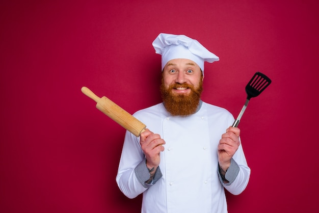 Gelukkige chef-kok met baard en rode schortchef-kok houdt houten deegroller vast
