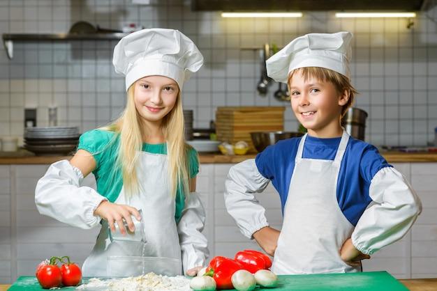 Gelukkige chef-kokjongen en meisje die bij restaurantkeuken koken