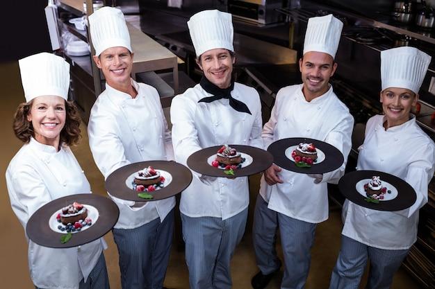 Gelukkige chef-koks die hun dessertborden voorstellen