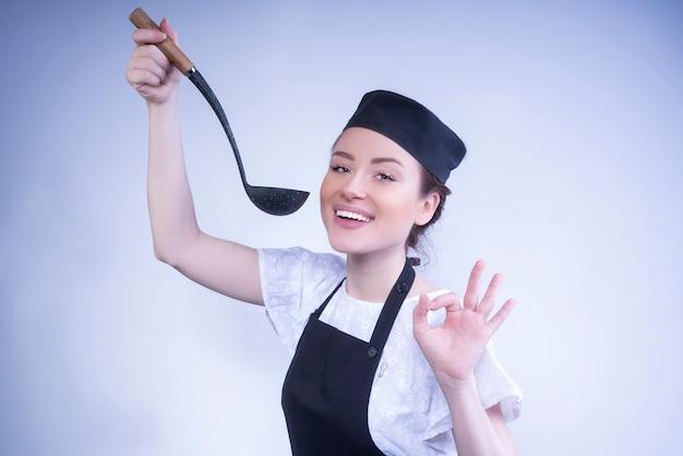 Gelukkige chef-kokvrouw die het ok gebaar met haar hand maakt.