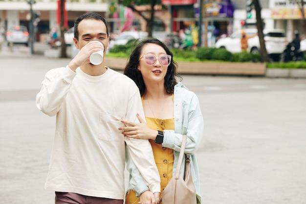 Gelukkige chinese jongeman die afhaalkoffie drinkt wanneer hij met een mooie vriendin op straat loopt