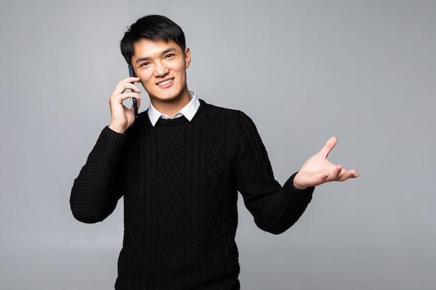 Gelukkige chinese mens die een smartphone gebruiken die tegen witte muur wordt geïsoleerd.