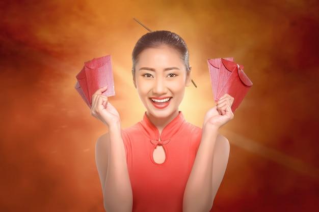 Gelukkige chinese vrouw die met cheongsam rode enveloppen houdt