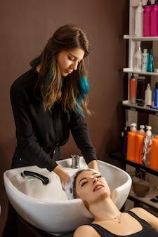 Gelukkige cliënt in een haarsalon die haar haar met shampoo wast.