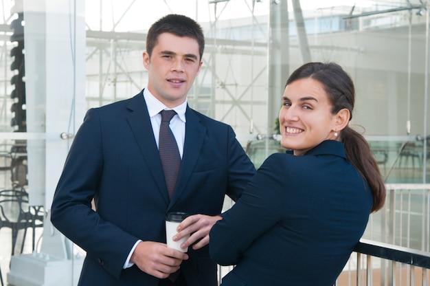 Gelukkige collega's die koffie drinken en bij camera in openlucht stellen