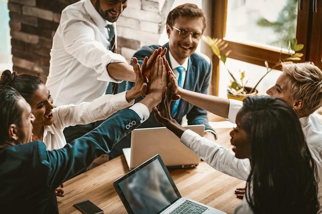 Gelukkige collega's die zich bij hun handen bij high five-gebaar voegen