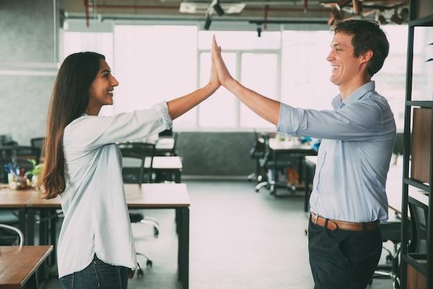 Gelukkige collega's geven vijf als symbool van succes