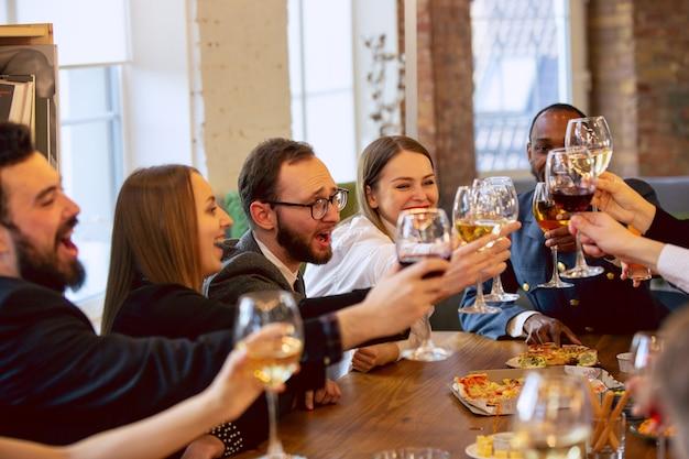 Gelukkige collega's vieren tijdens bedrijfsfeest en bedrijfsevenement. jonge blanke mensen in zakelijke kleding juichen, lachen. concept van kantoorcultuur, teamwork, vriendschap, vakantie, weekend.