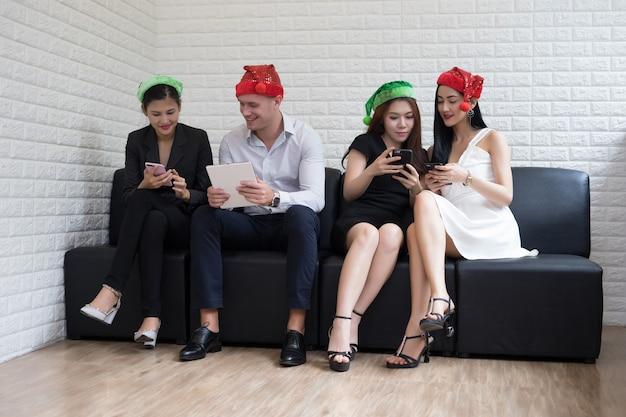 Gelukkige commerciële groepsmensen in santahoed die pret hebben voor de partij van beroemdheidskerstmis.