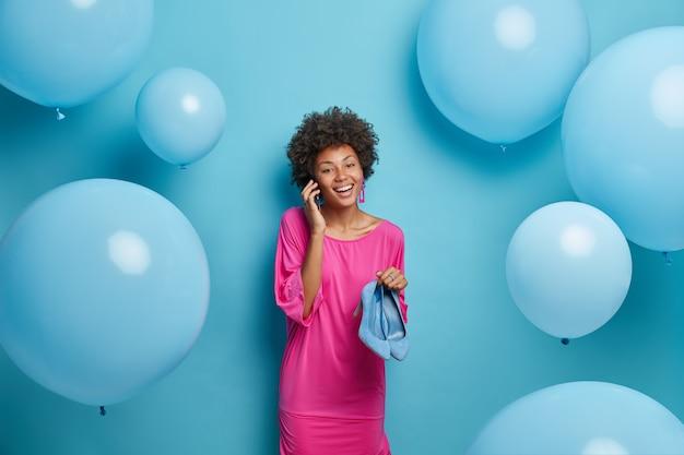Gelukkige dame bespreekt haar formele ontmoeting met collega, draagt roze elegante jurk, houdt hoge hak blauwe schoenen, viert nieuwe baan, nodigt vrienden op feest uit, poseert rond grote ballonnen