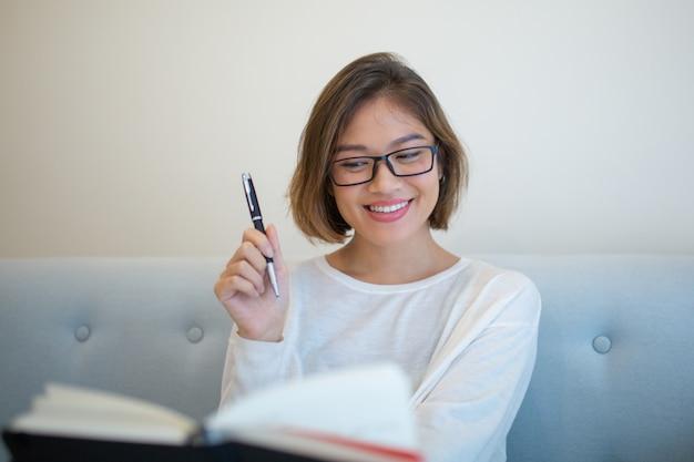 Gelukkige dame die pen opheft en boek op bank thuis leest