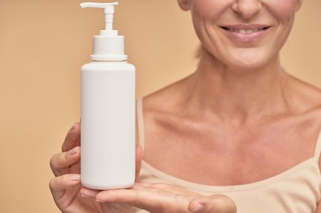 Gelukkige dame die pronkt met een vochtinbrengende lichaamscrème in de studio