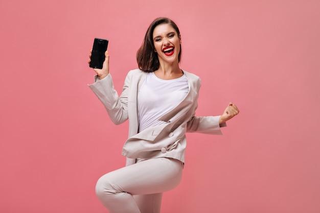 Gelukkige dame in beige pak vormt met telefoon op roze achtergrond. het vrolijke meisje in bureaukleding en met rode lippen houdt smartphone.