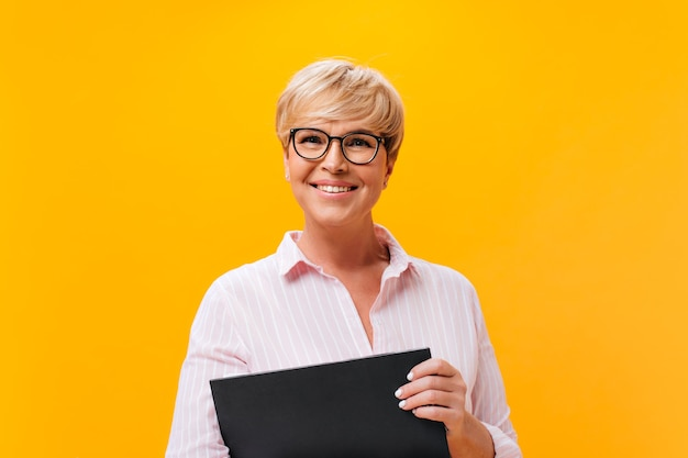 Gelukkige dame in brillen en roze overhemd die op oranje achtergrond glimlachen
