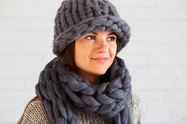 Gelukkige dame in hoed en sjaal