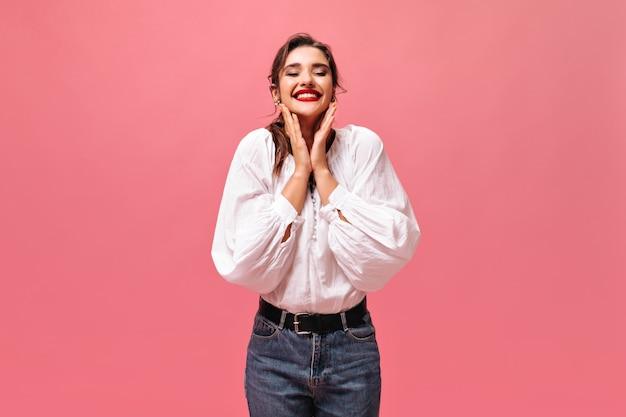 Gelukkige dame in jeans en wit overhemd die op roze achtergrond glimlachen. vrolijke mooie vrouw met donker haar in modieuze jurk kijkt naar de camera.