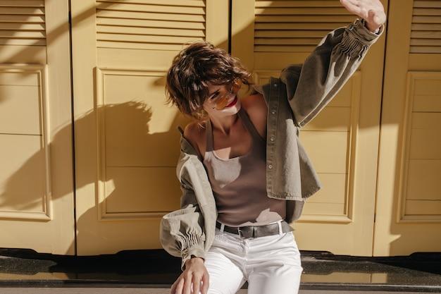 Gelukkige dame in zonnebril en jasje glimlacht op gele deuren. trendy vrouw met krullend haar in onderhemd vormt op gele deuren
