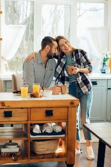 Gelukkige dame met een kopje thee leunend naar haar lachende vriendje en knuffelen zijn schouder