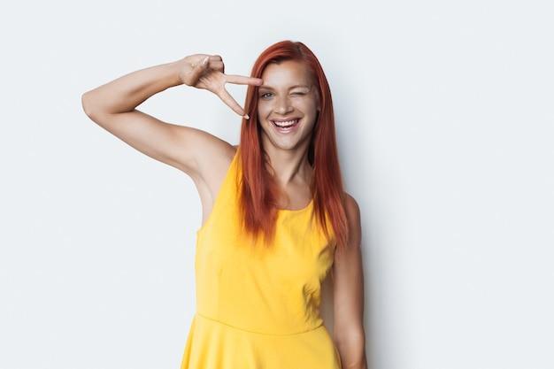 Gelukkige dame met rood haar die op een witte muur glimlachen die het vredesteken met twee vingers gebaart