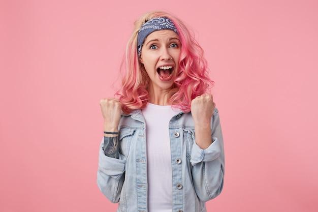 Gelukkige dame met roze haar en getatoeëerde hand, staand, gekleed in een wit t-shirt en een spijkerjasje. schreeuwend en viert overwinning van favoriete voetbalteam met vuisten.