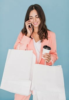 Gelukkige dame met winkelnetten praten op smartphone