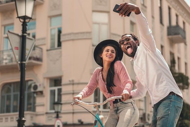 Gelukkige dame op een fiets en haar man die selfie neemt en de tong laat zien