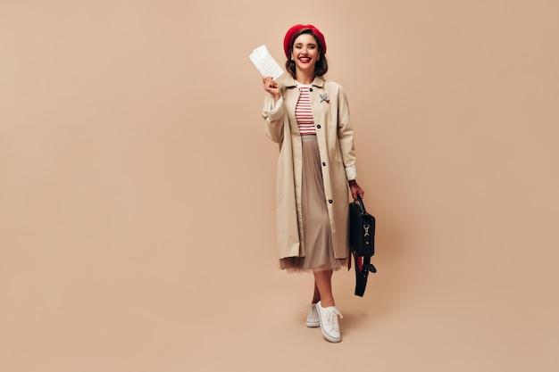 Gelukkige dame op rode baret en loopgraaf vormt met kaartjes op beige achtergrond. vrolijke jonge vrouw in lange stijlvolle rok en herfstjas kijkt naar de camera.