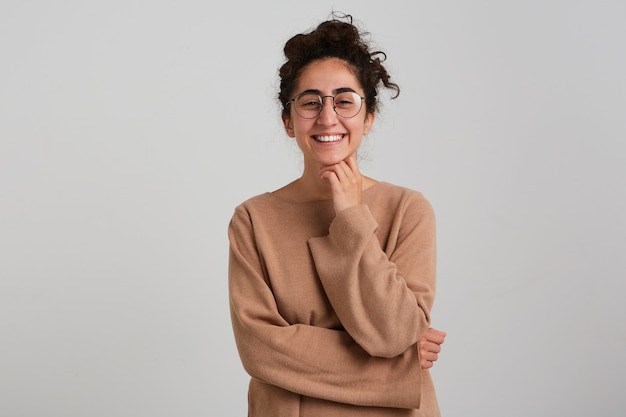 Gelukkige dame, positieve vrouw met donker krullend haarbroodje, beige trui en bril dragen