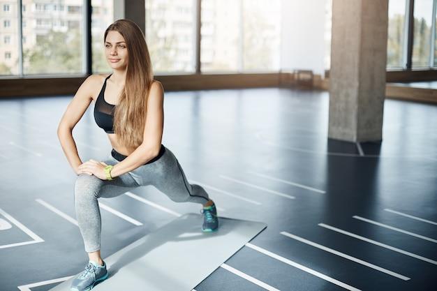Gelukkige dame van de fitnesscoach die zich uitstrekt voordat ze mensen traint om een perfect evenwicht tussen lichaam en ziel te bereiken.