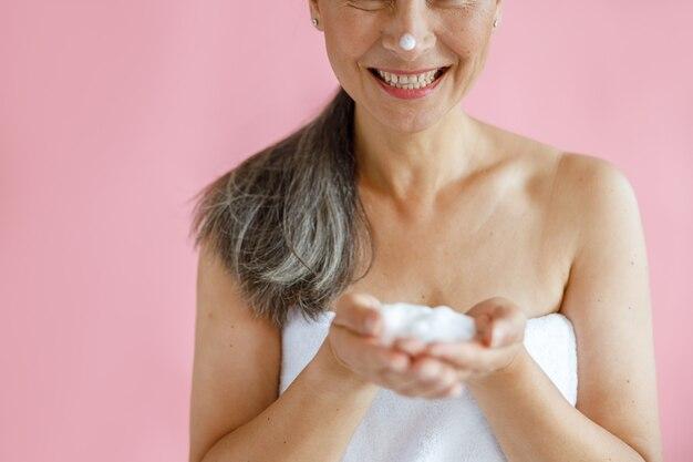 Gelukkige dame van middelbare leeftijd met witte handdoek en grijze paardenstaart toont handvol schuim op roze achtergrond in studio close-up. volwassen schoonheid levensstijl