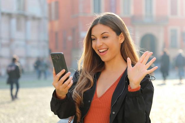Gelukkige damegroet tijdens een videogesprek met een slimme telefoon op stadsstraat