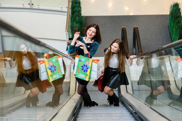 Gelukkige dames glimlachend en winkelen in de mall
